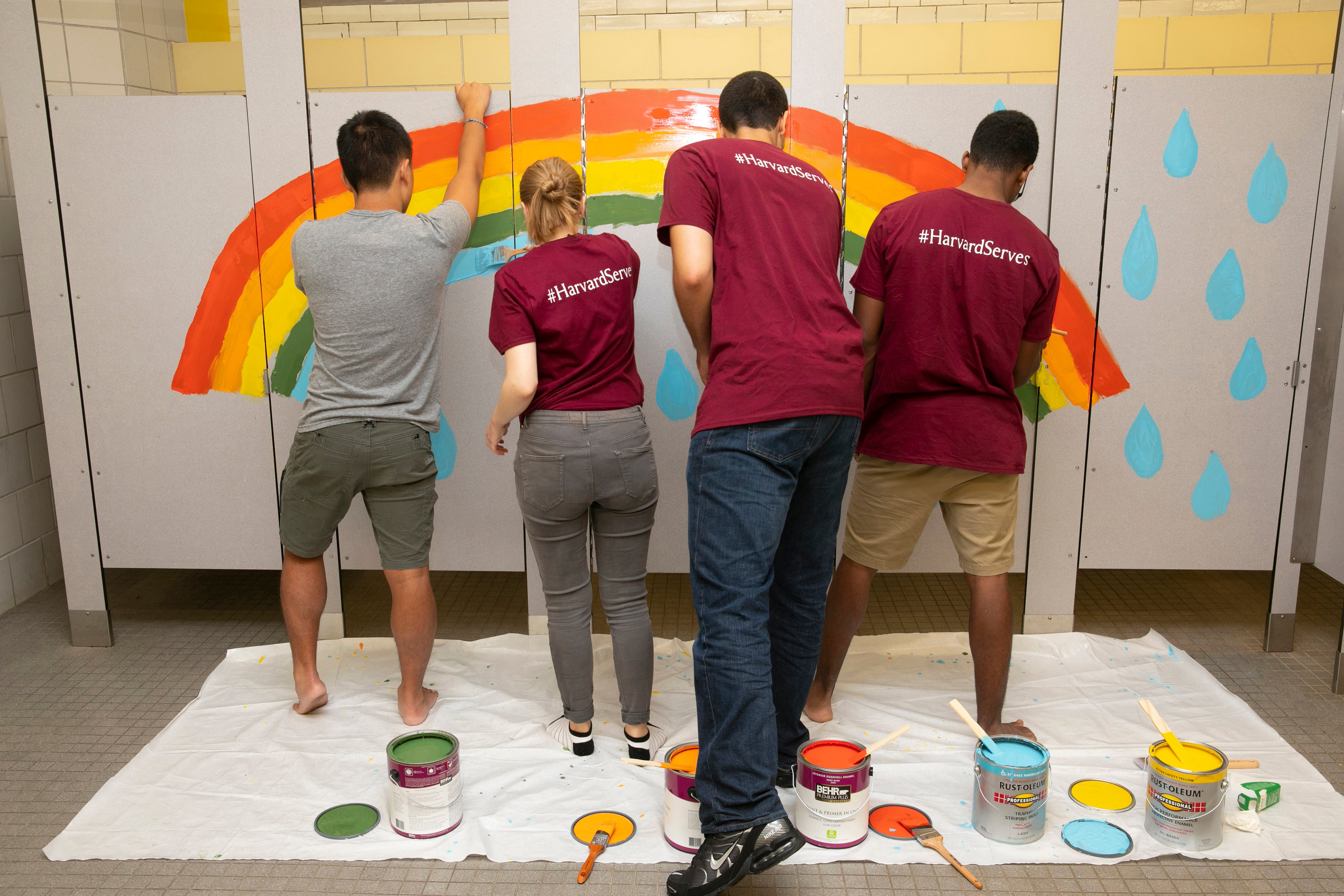 Students paint bathroom stall doors.