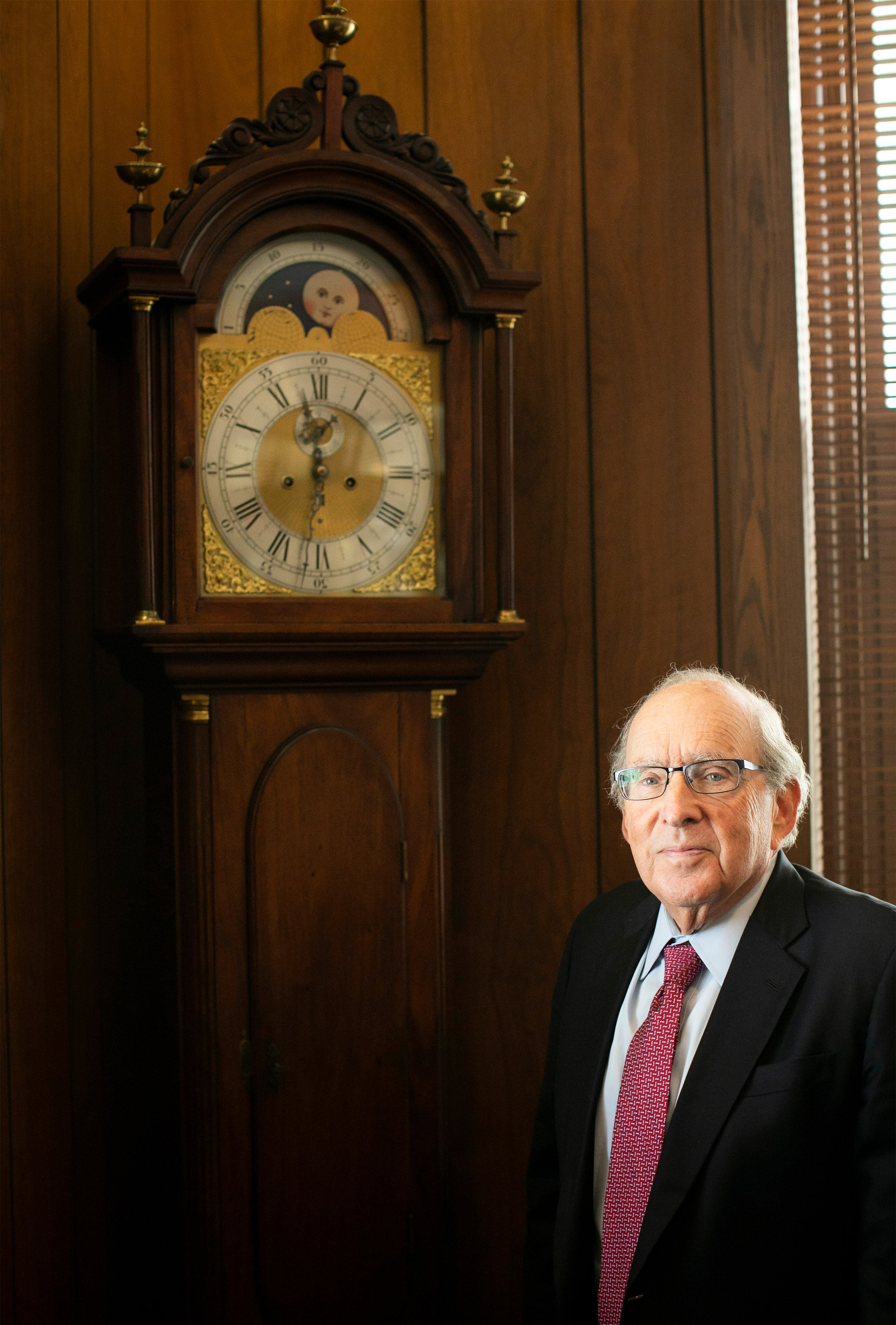 Dean Bruce Donoff standing in front of an antique grandfather clock.