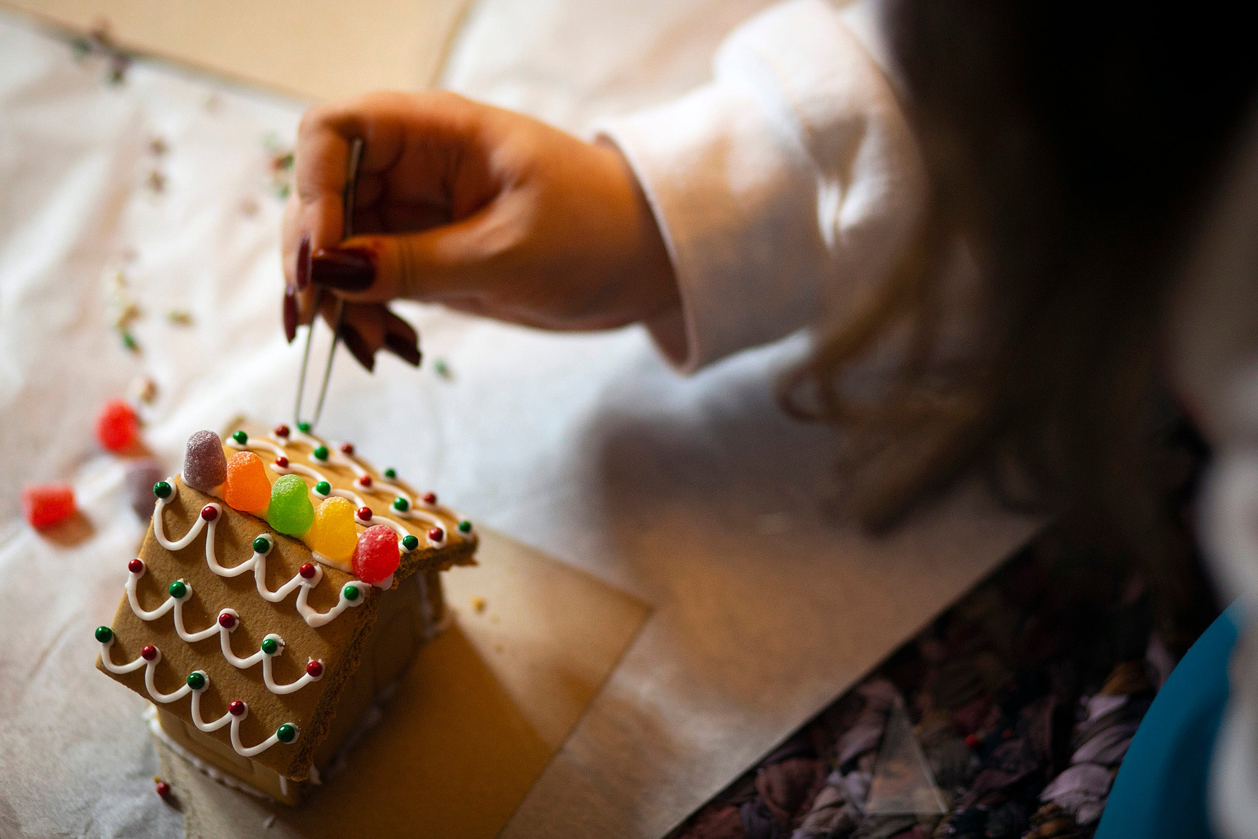 Final touches on a gingerbread house.