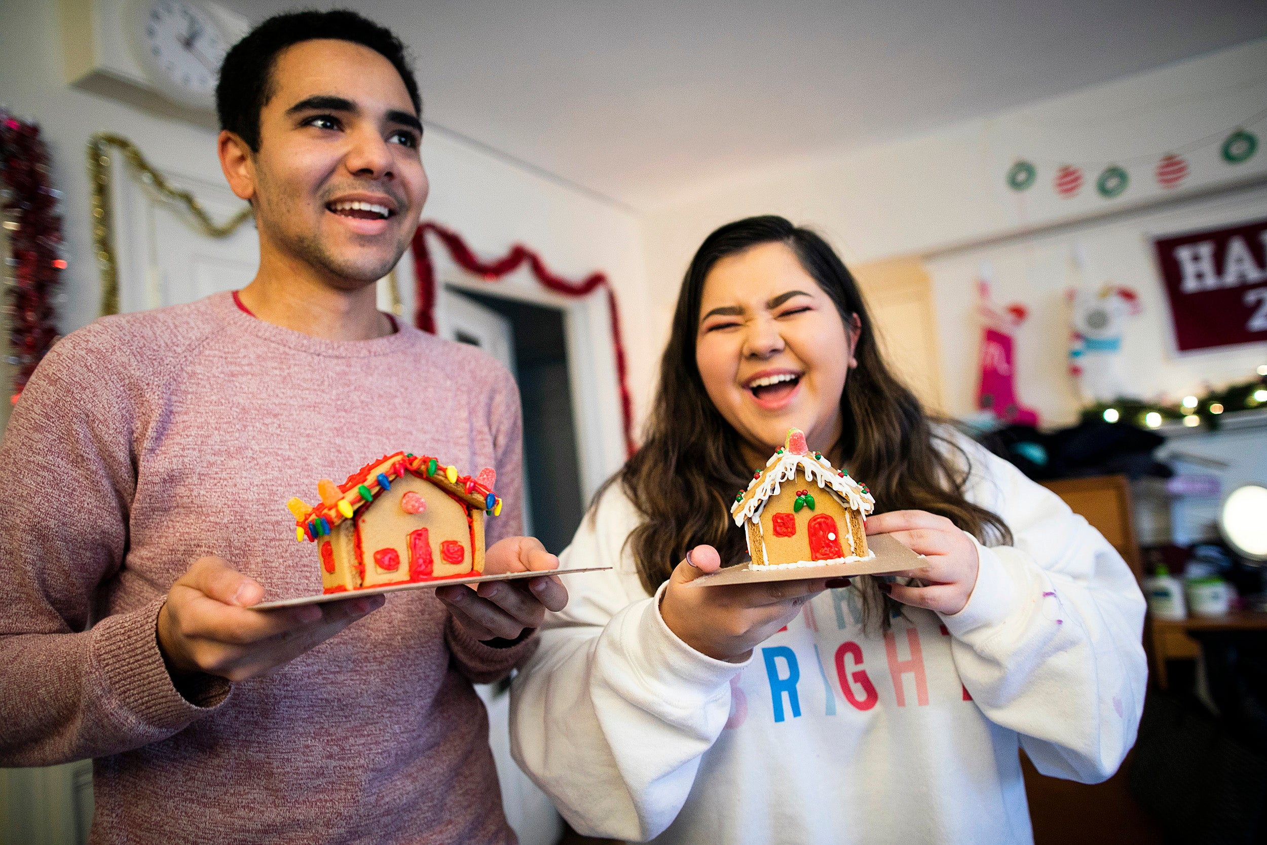 Two students holding gingerbread houses.