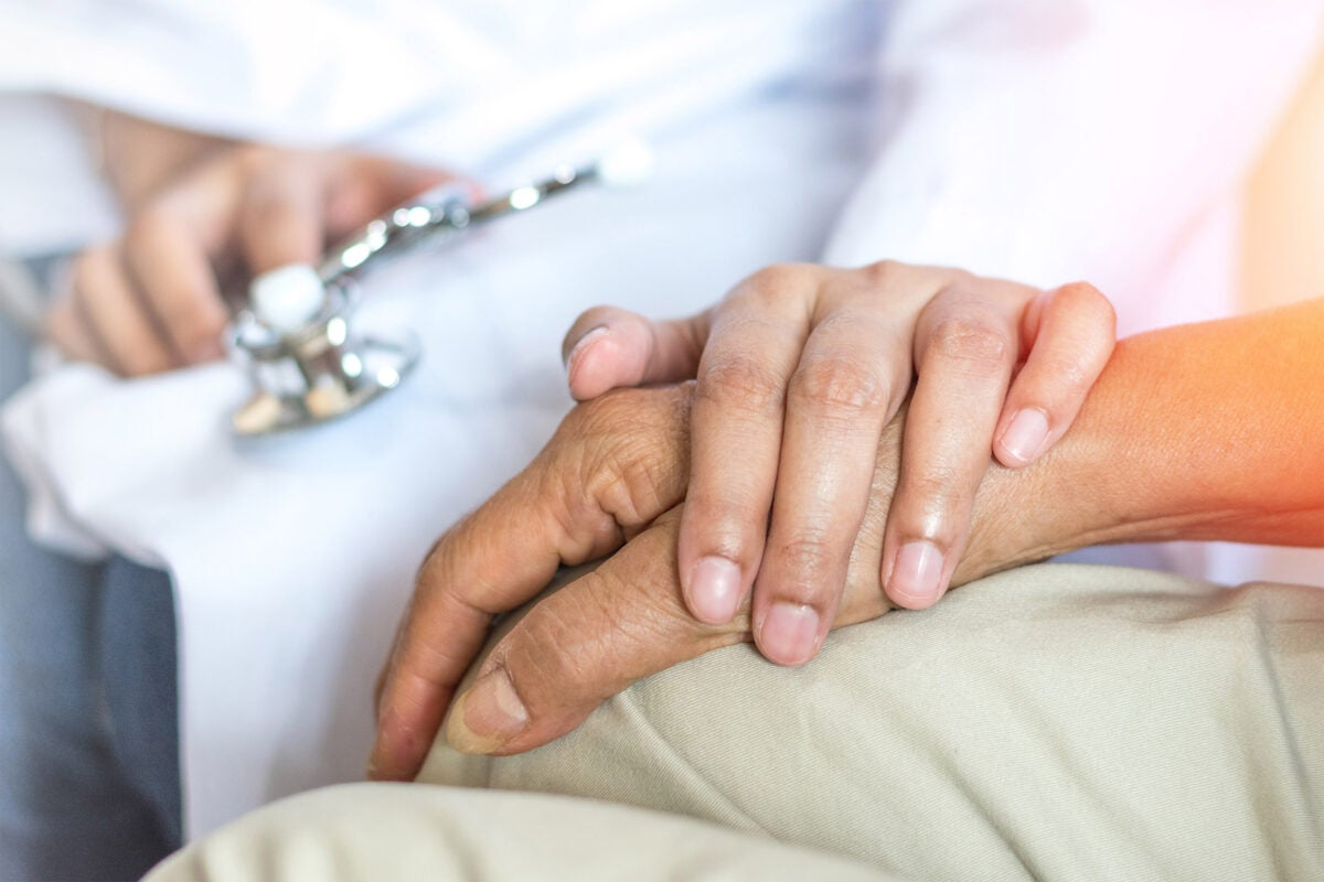 Doctor holding hand of patient.