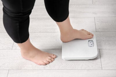 Overweight woman using scales indoors.
