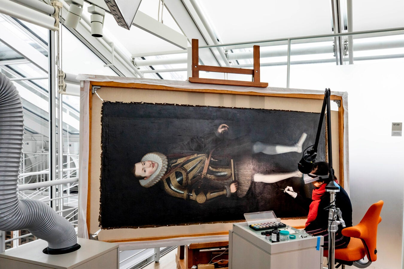 Curator restores a large painting.