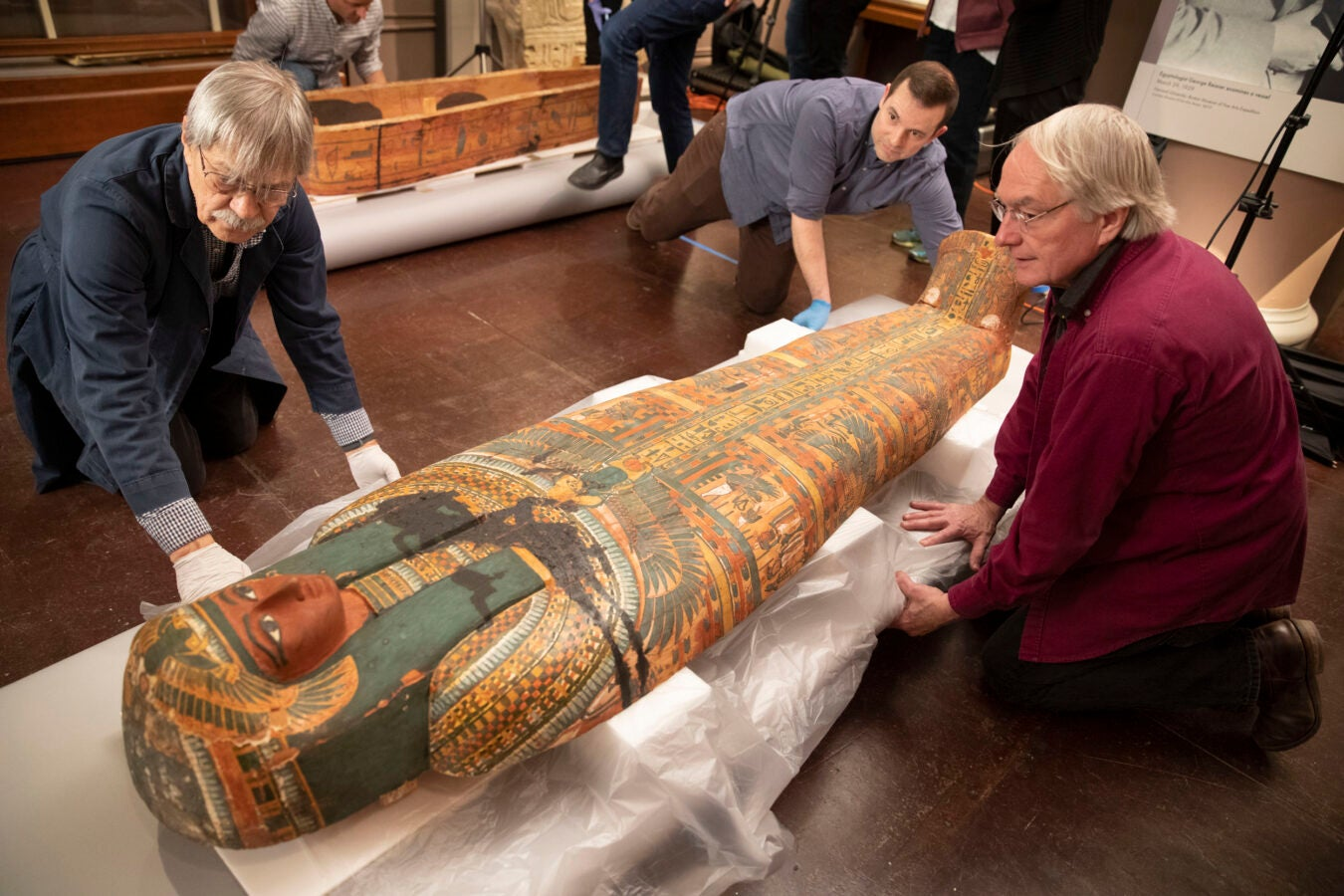 Conservators carefully position colorful closed coffin of Ankh-khonsu.
