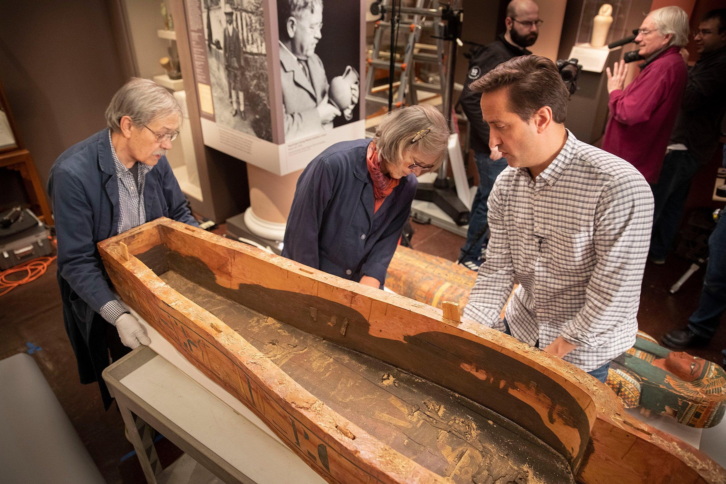 Dennis Piechota (left), Jane Drake, and Adam Aja view the interior of the coffin of Ankh-Khonsu. Kris Snibbe/Harvard Staff Photographer