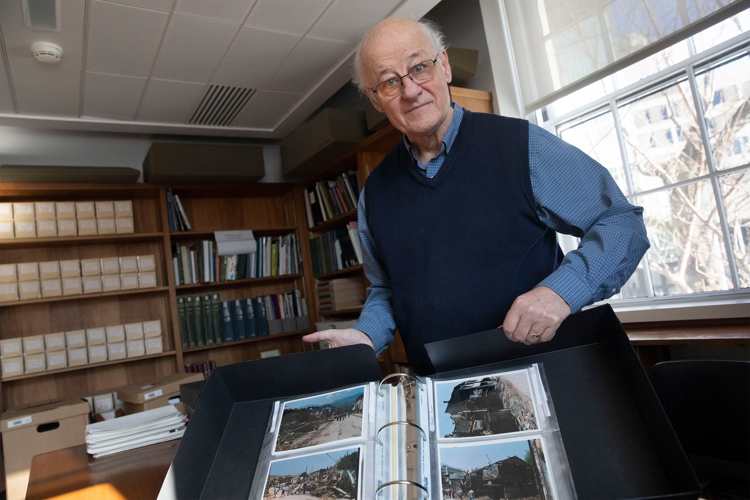 András Riedlmayer holding photo album.