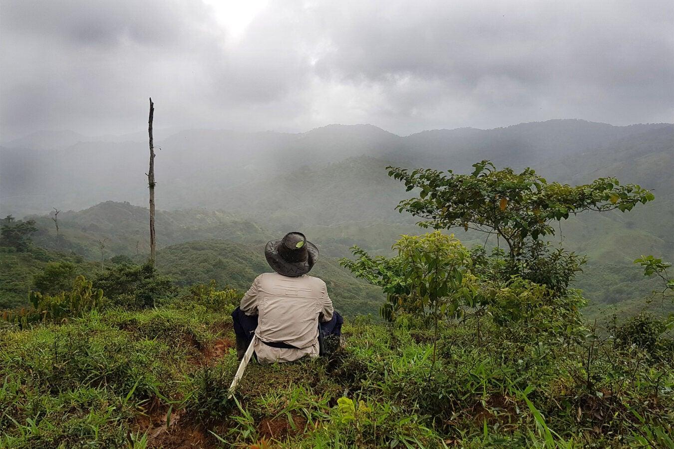 Man sitting looking at mountains.