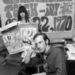 Denis Hayes on phone as associate holds posters advertising Environmental Teach-In in 1970.