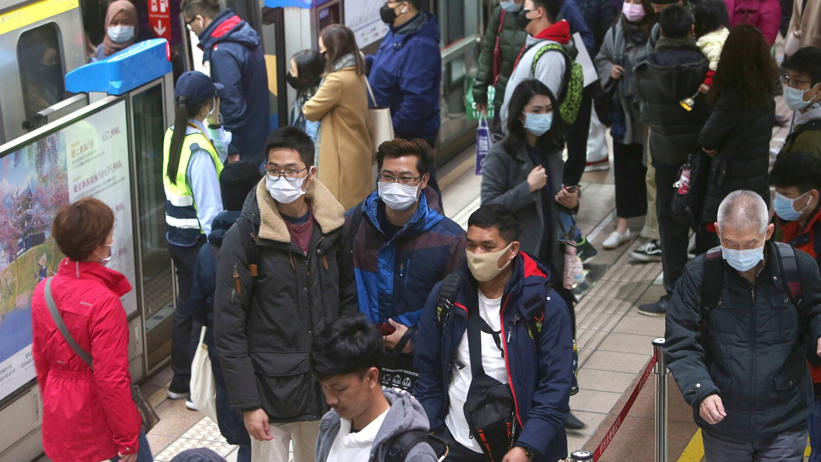 People with masks on at a Chinese metro station.
