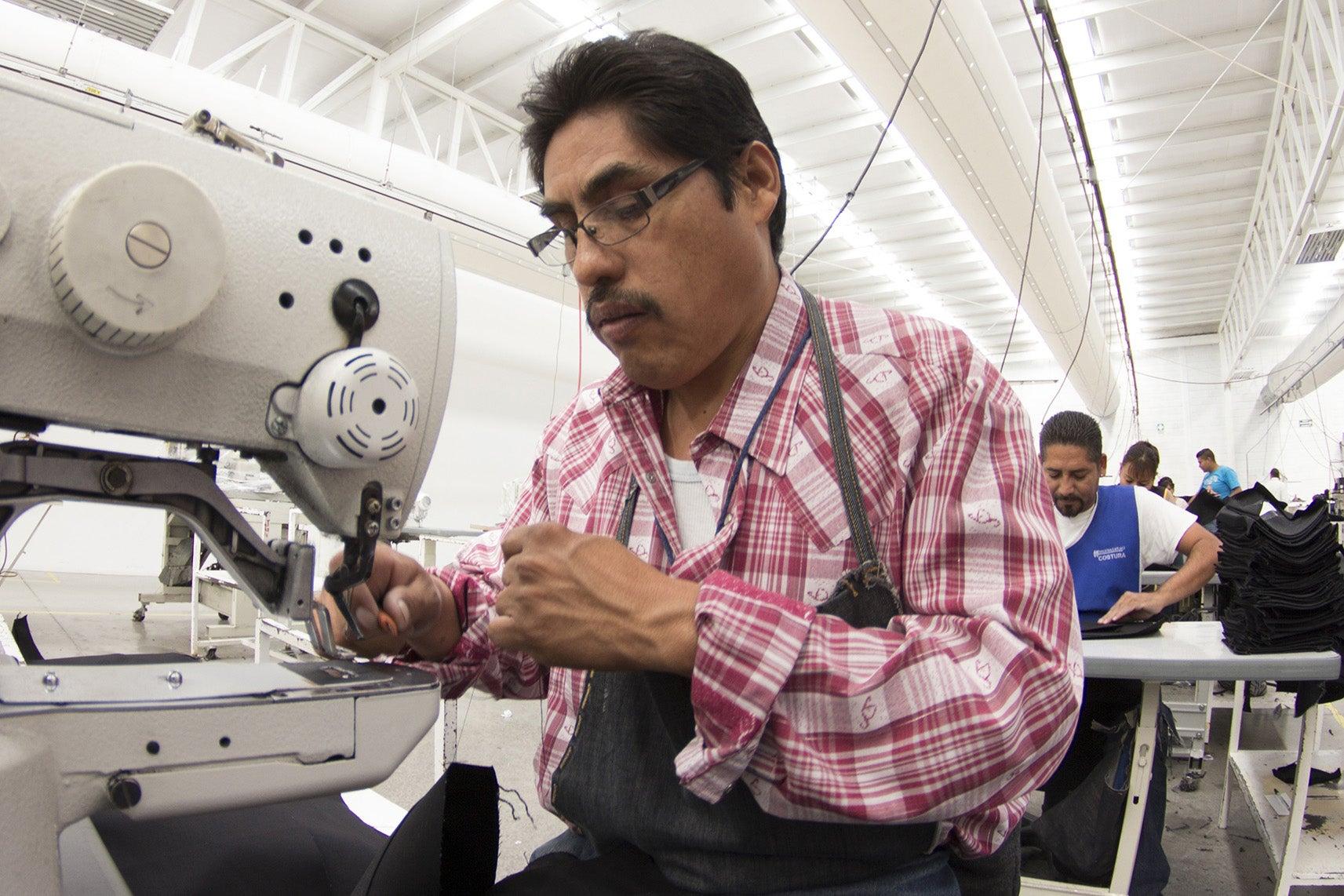 Man using sewing machine.