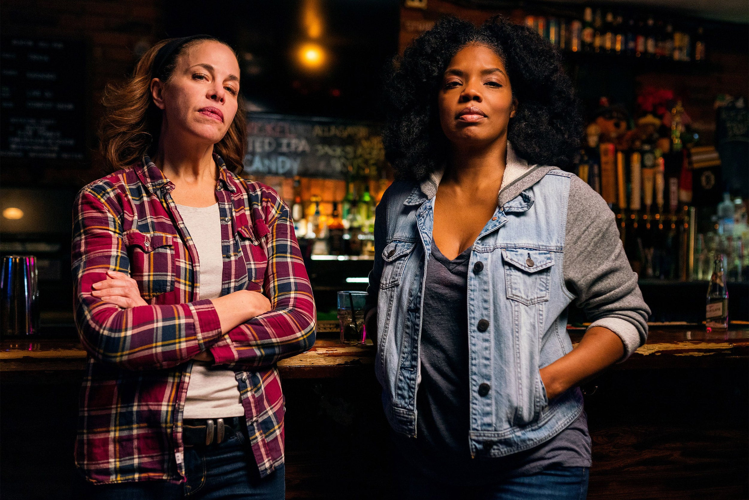 Two women standing in a bar.