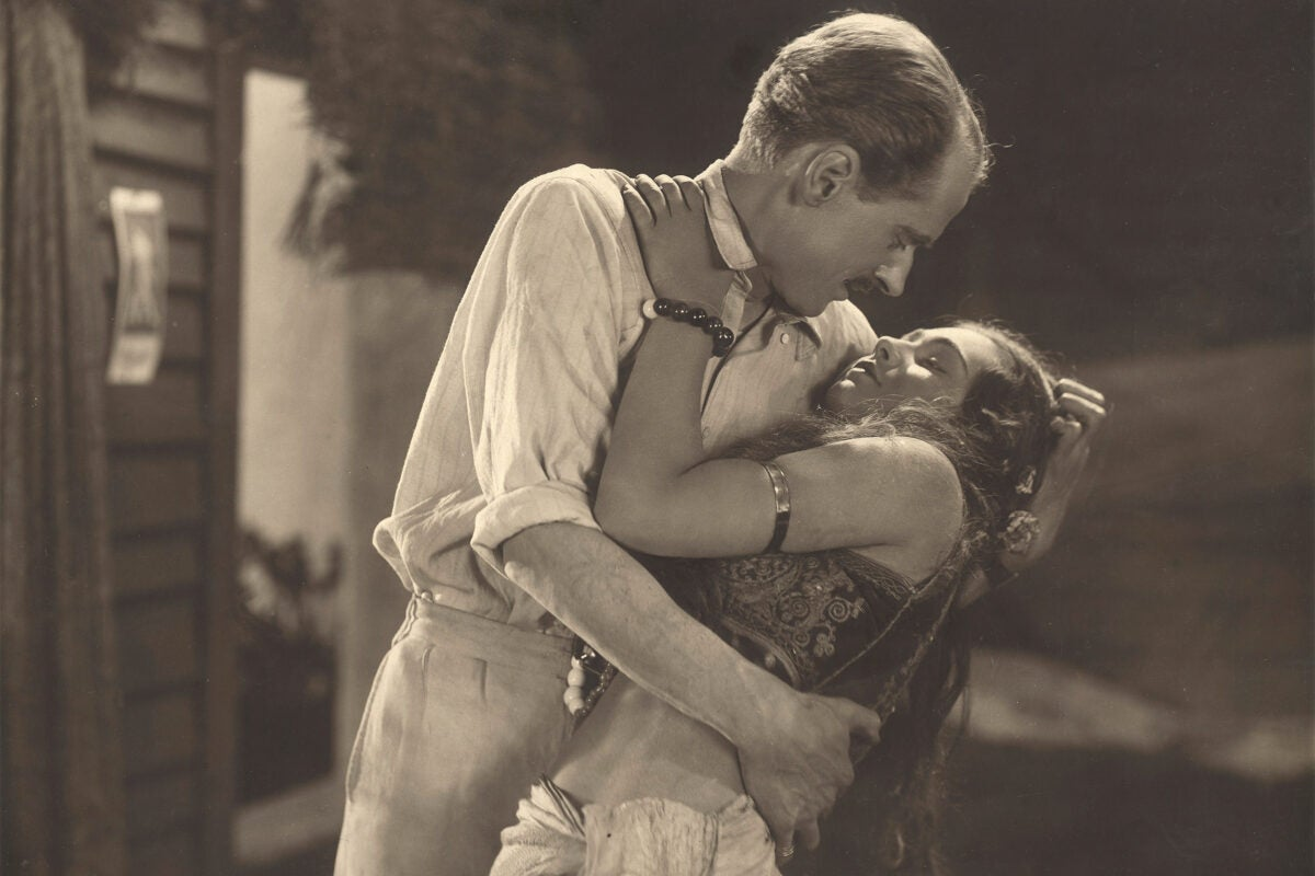 "Man embracing woman in still from ""The Pleasure Garden."""