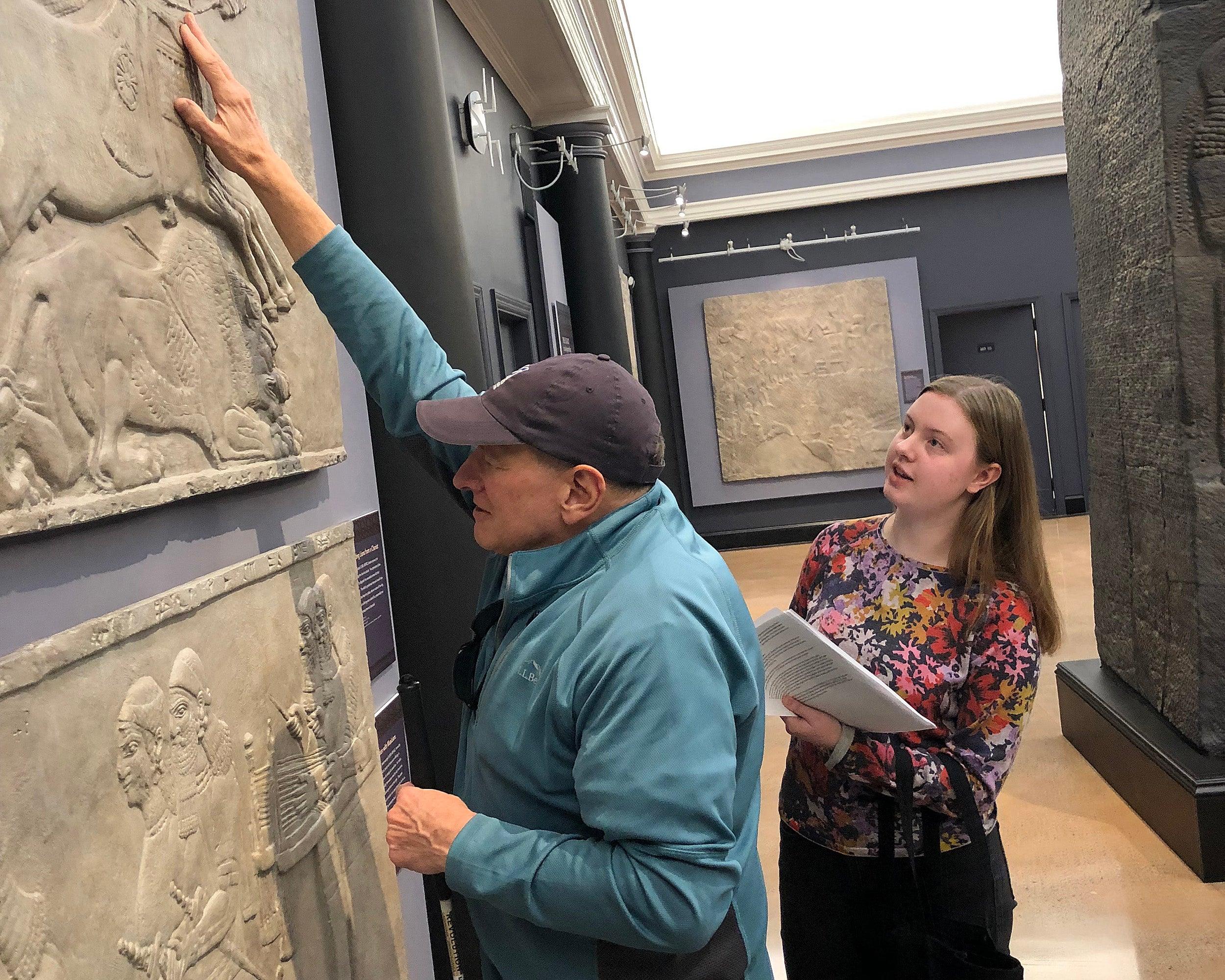 Visitor touches exhibit piece.