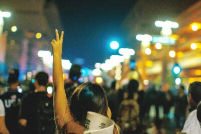 Person holding up peace sign.