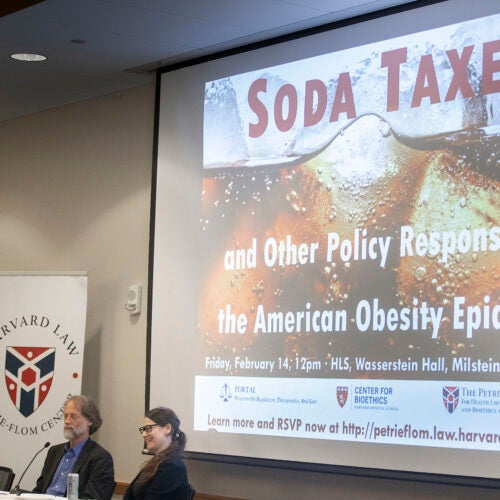 Three people sitting in front of a screen with Soda Taxes on it.