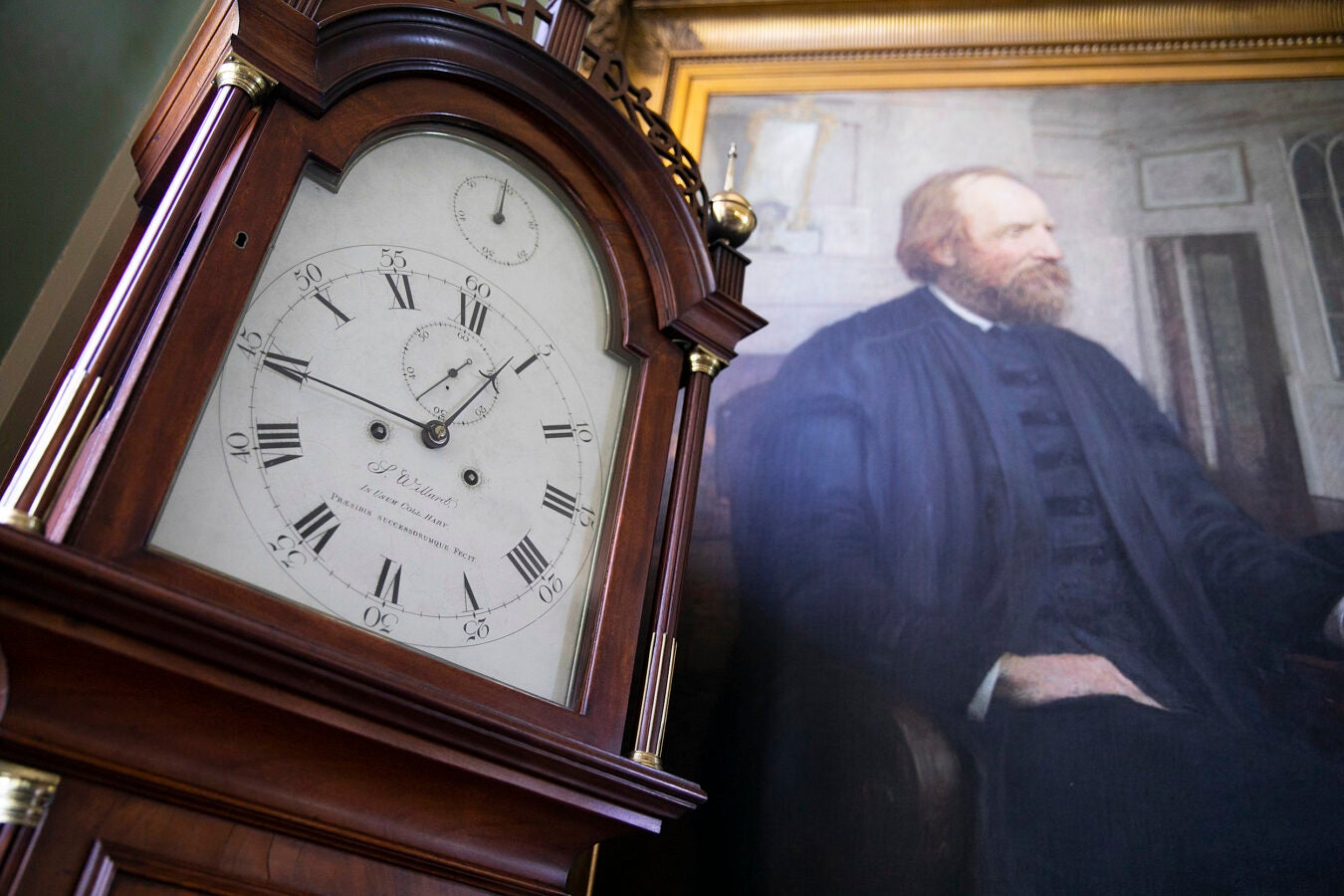 Clock next to a portrait.