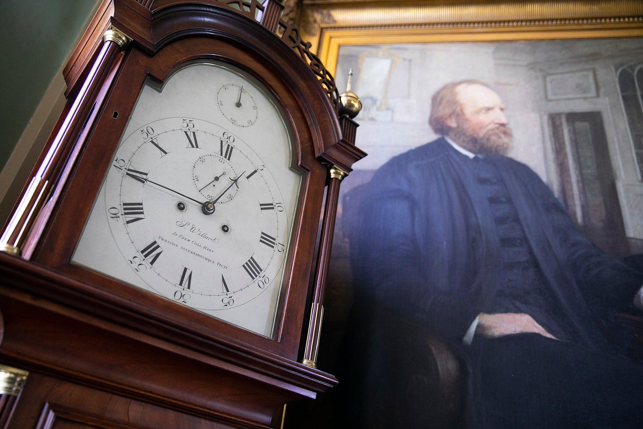 Clock next to a portrait.