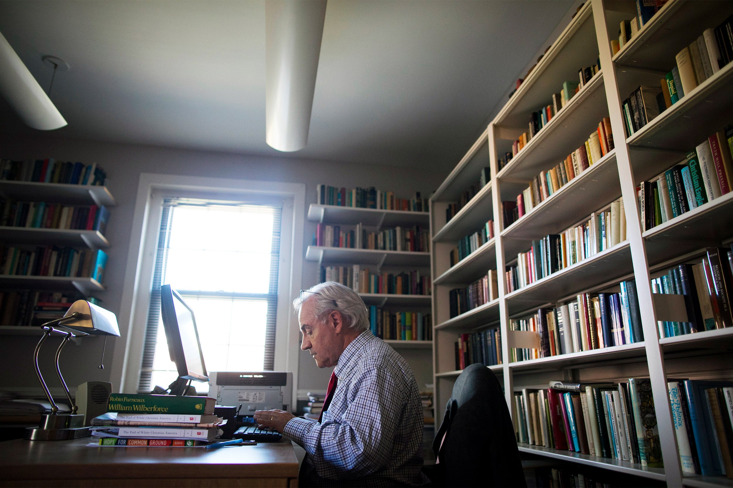 E.J. Dionne typing in his office.