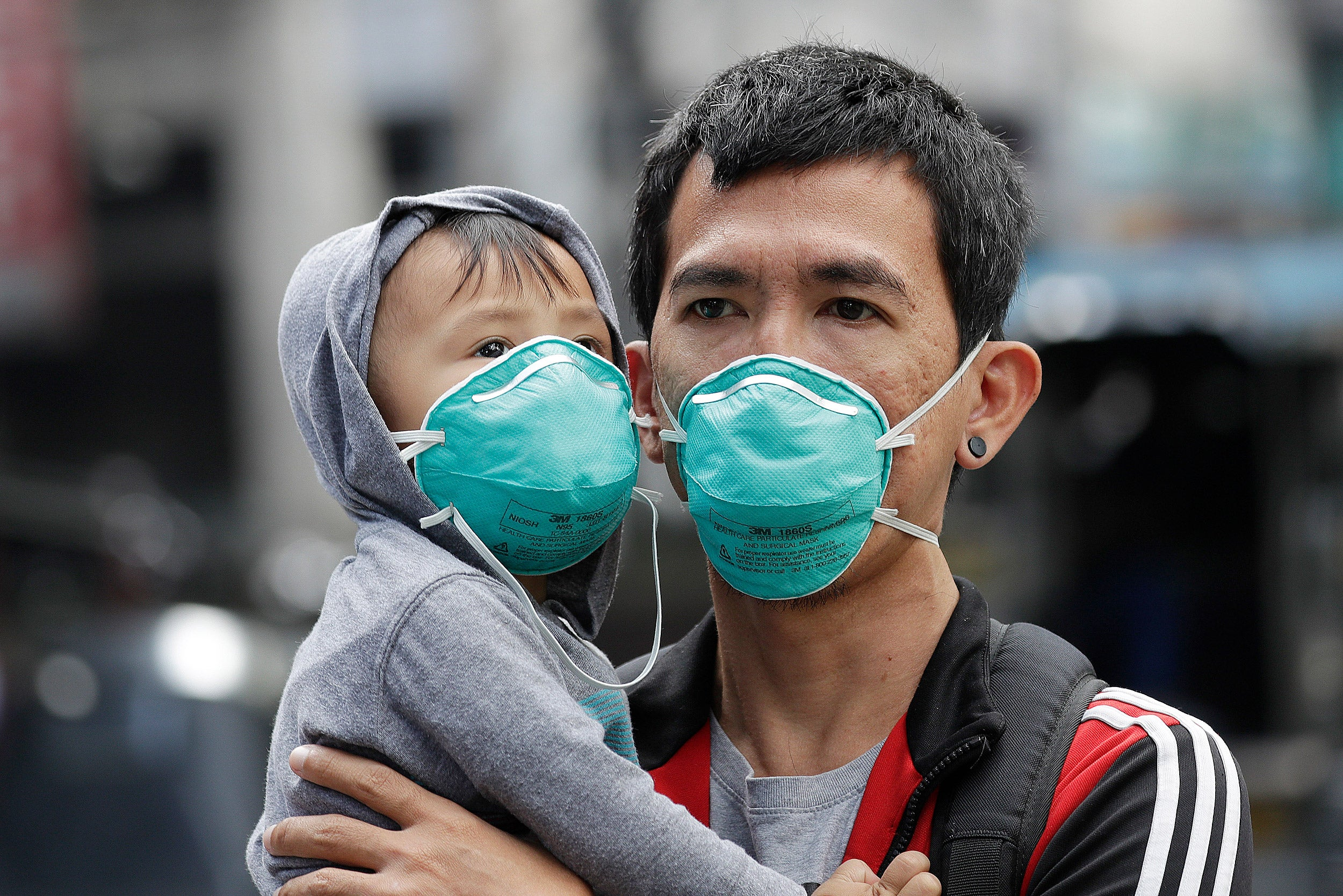 Adult and child wearing flu masks.