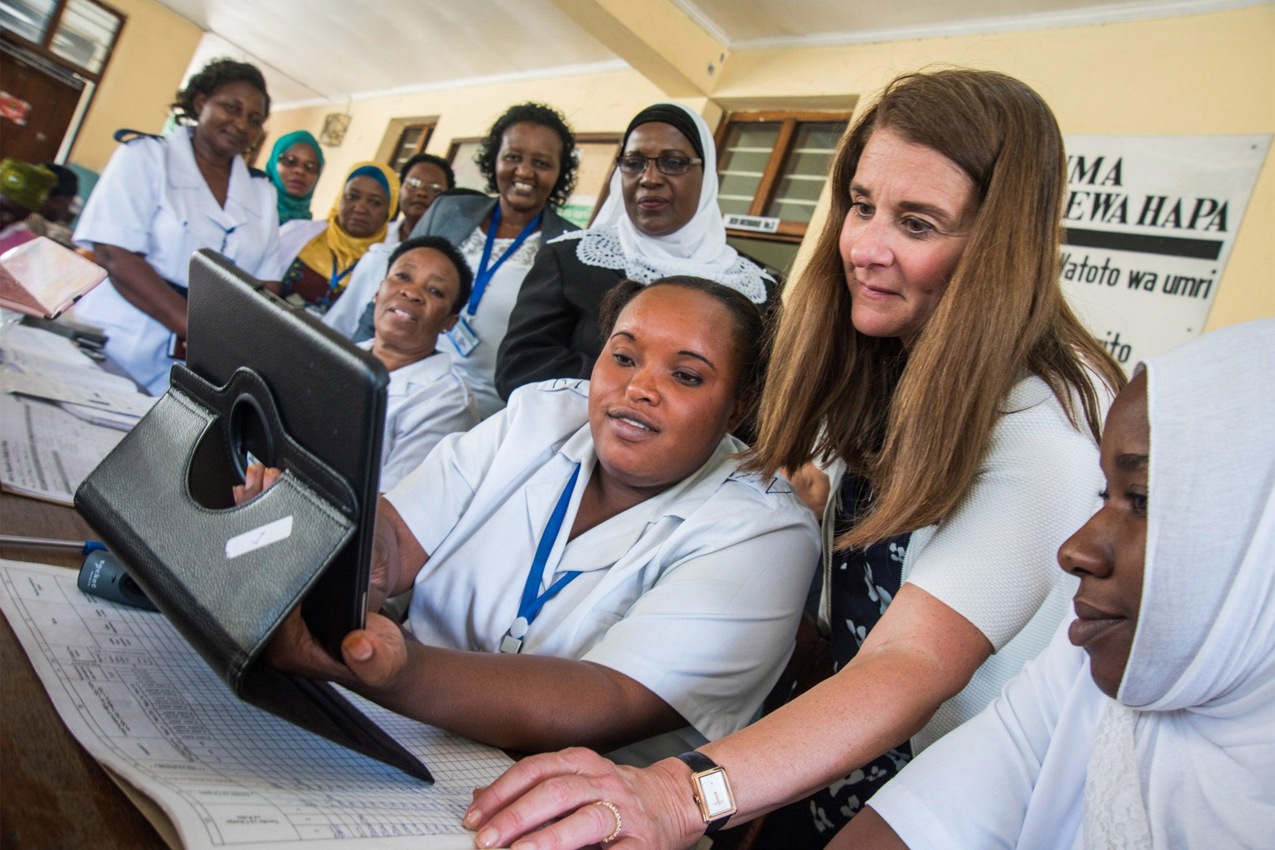 Melinda Gates looking at a computer with nurses in Tanzania.