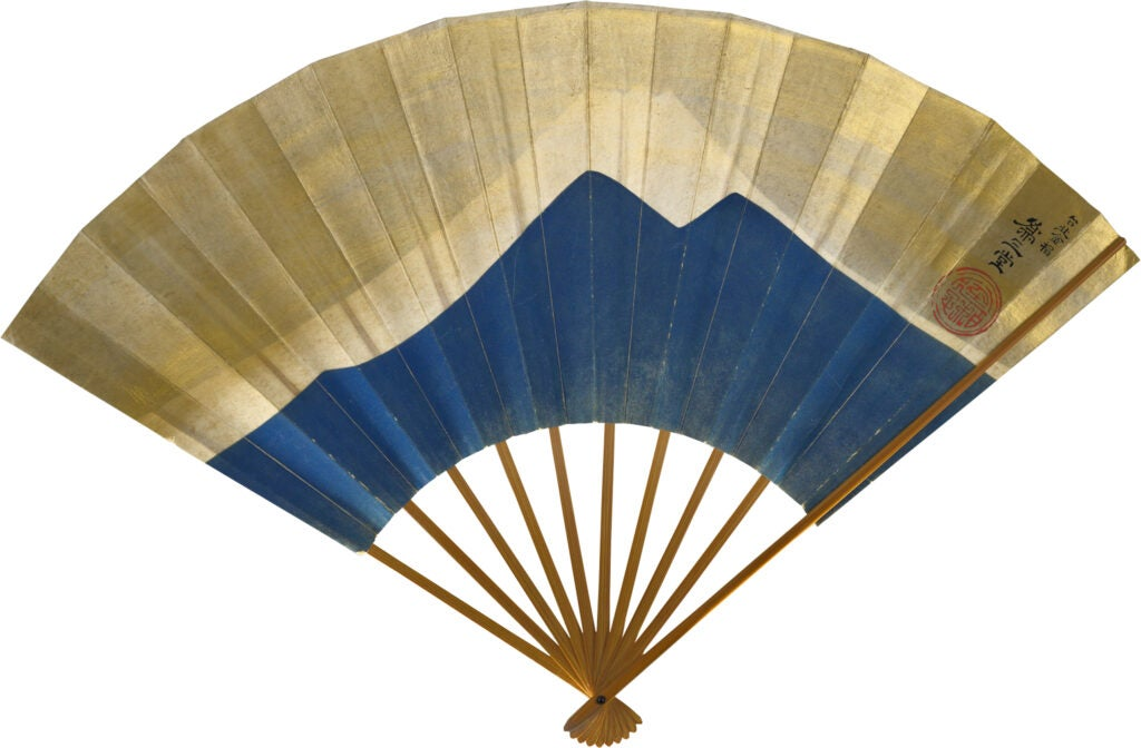 folding fan painted with blue silhouette of mountain.