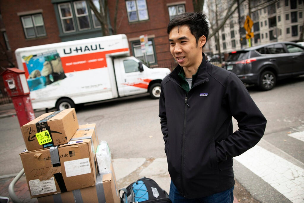 Victor Qin stands with boxes by a moving truck.