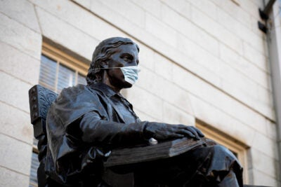 John Harvard Statue with mask on.