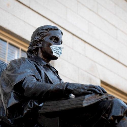 John Harvard Statue with mask on.