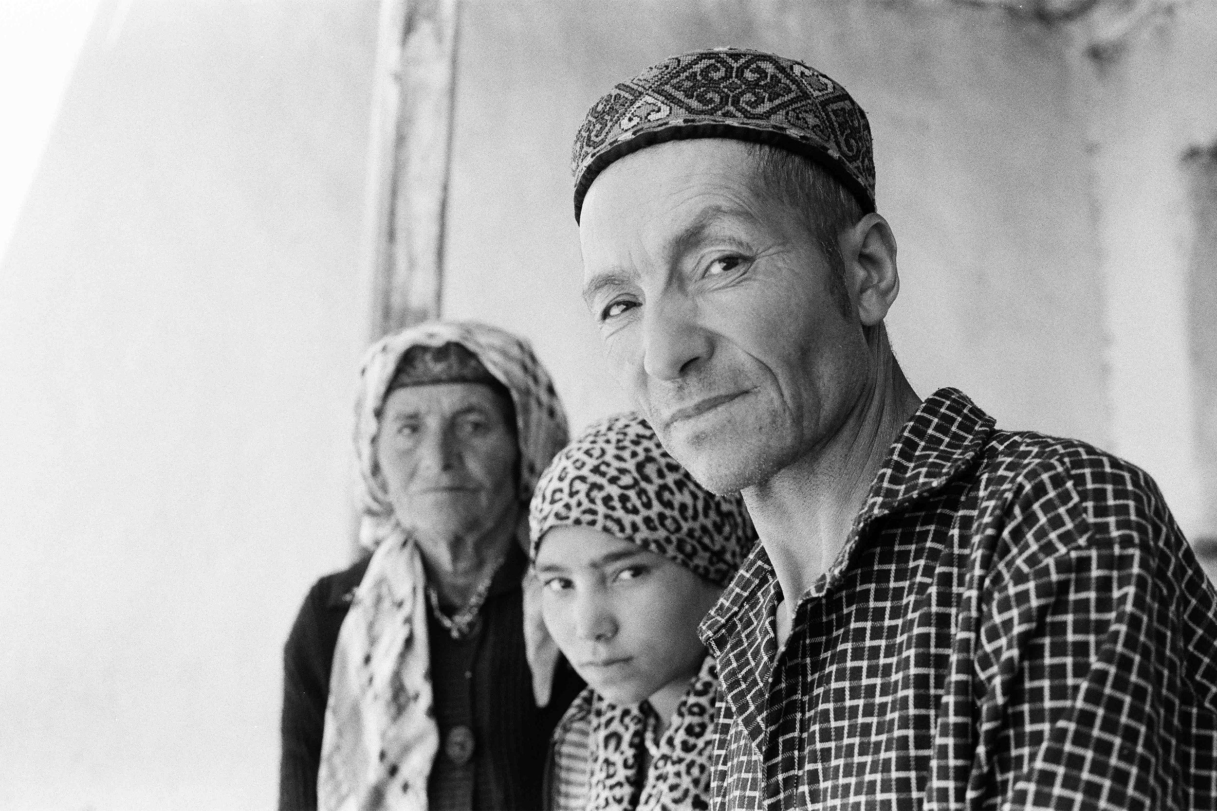 Qurbonsho, sitting beside his daughter and aunt, in front of his ancestral home.