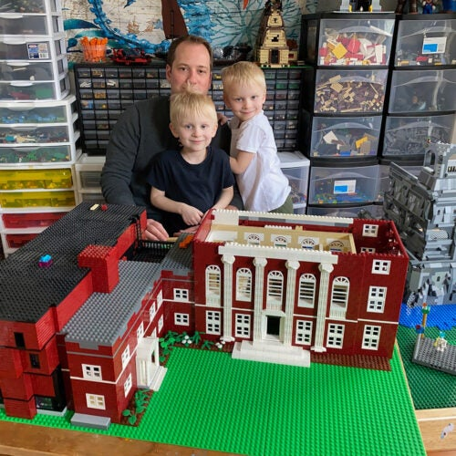 Jonathan Savilonis and sons Julius and Lysander with their LEGO model of Harvard's Music Building.