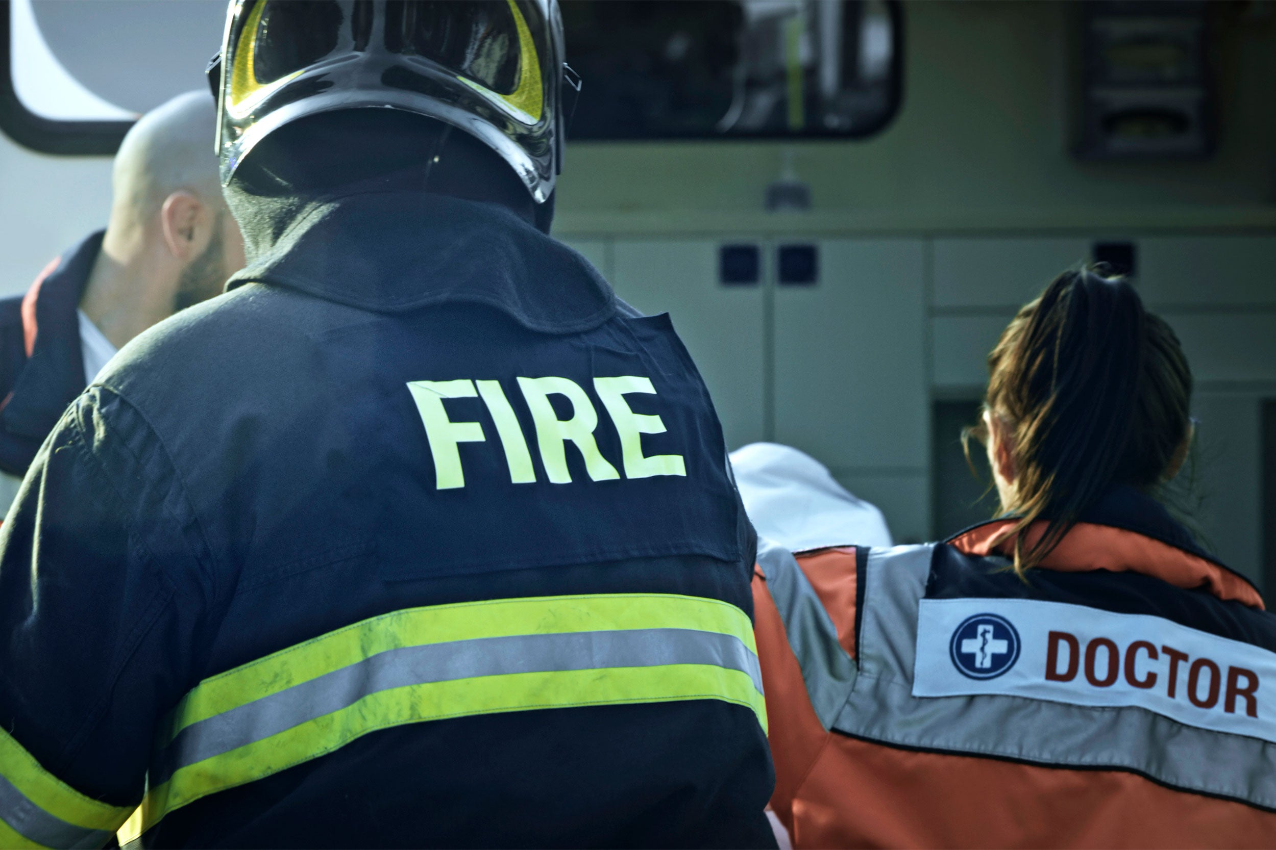 Fireman, EMT and doctor next to ambulance.