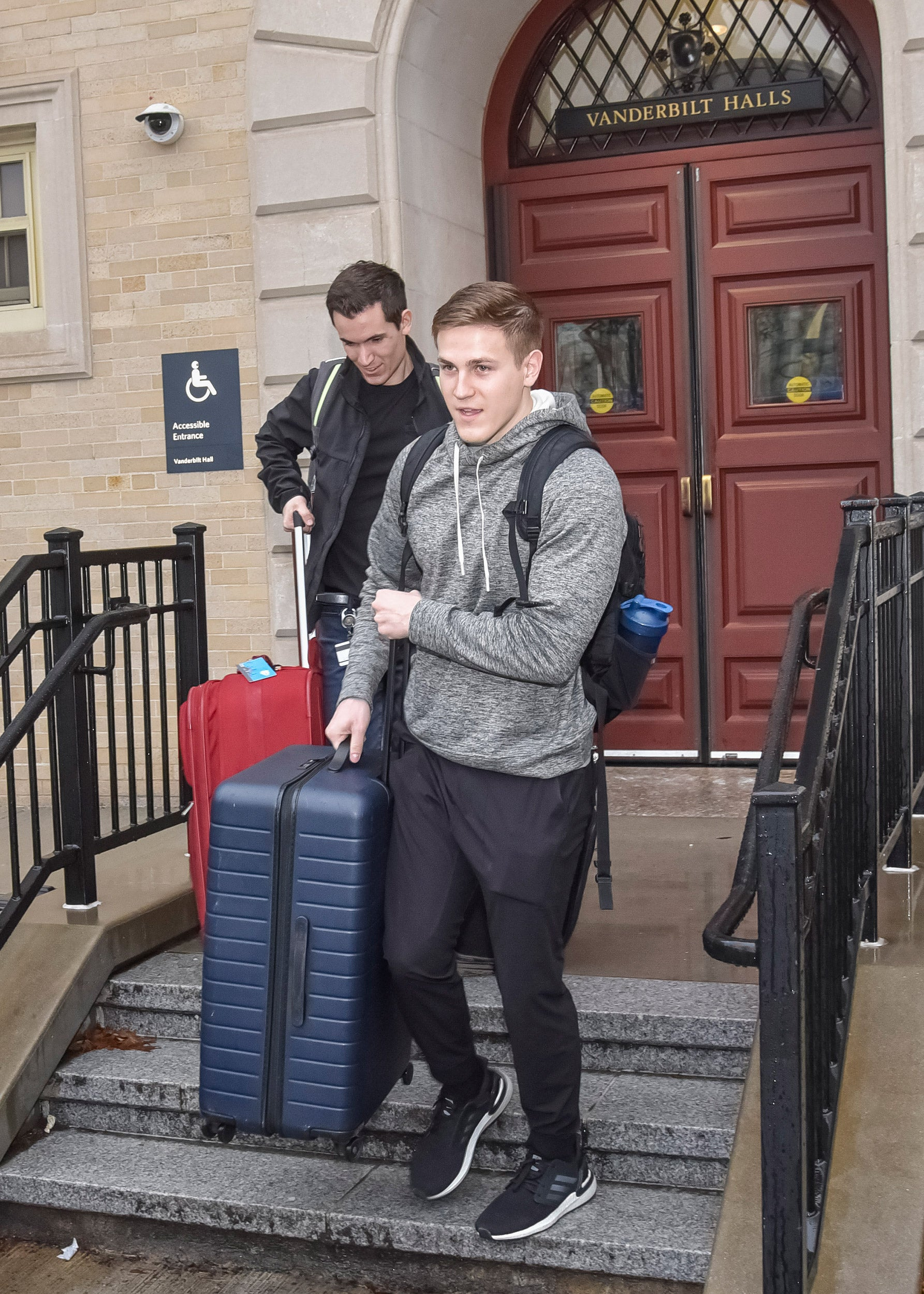 Two students with suitcases.