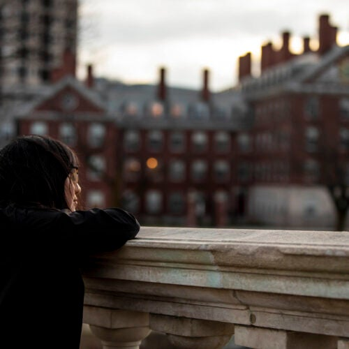 Student staring out over the Charles River.