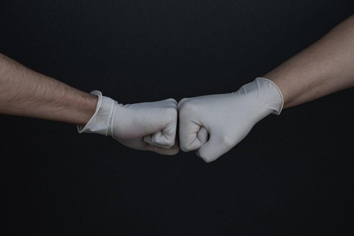 Fist bump wearing gloves.
