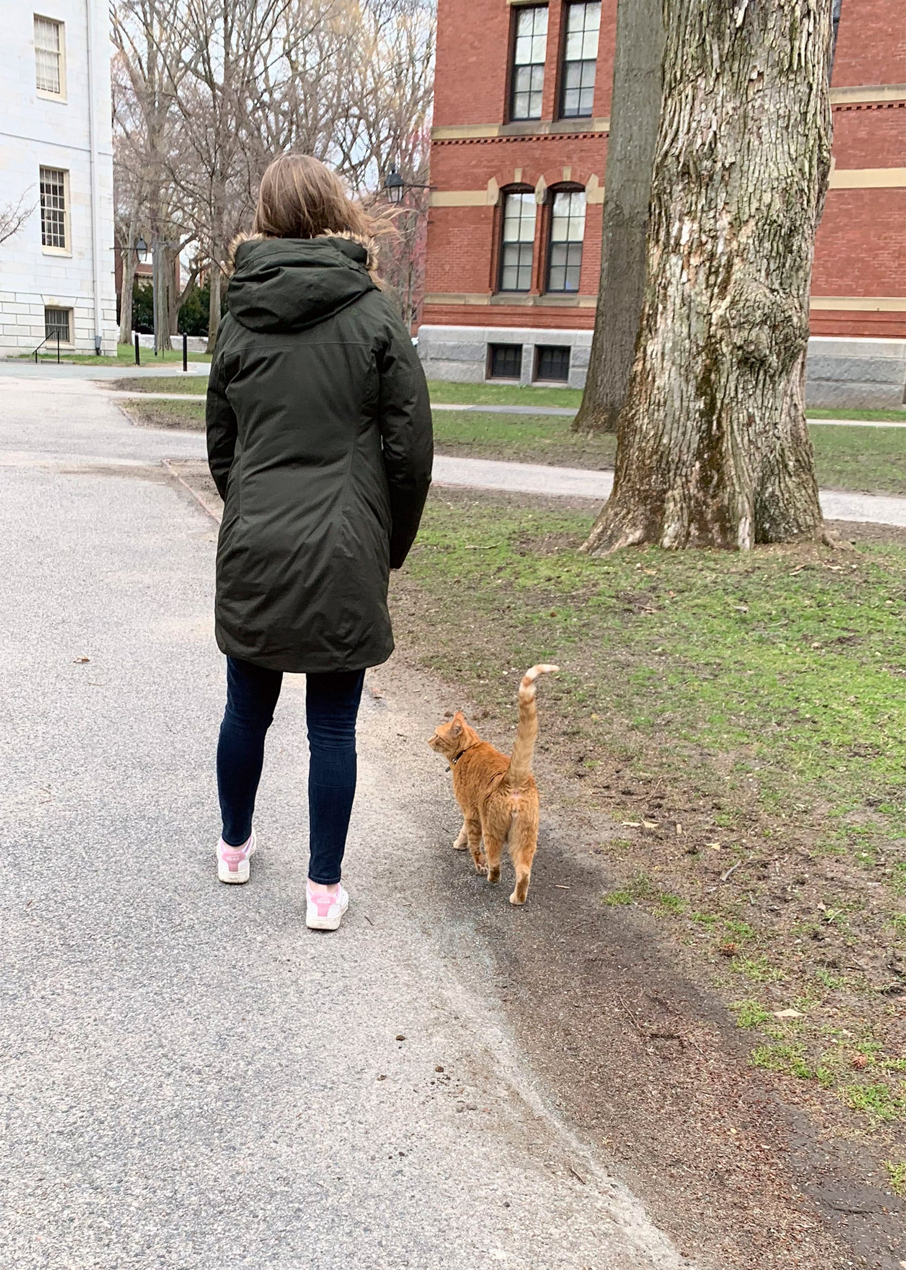 Student walking with Remy the cat.