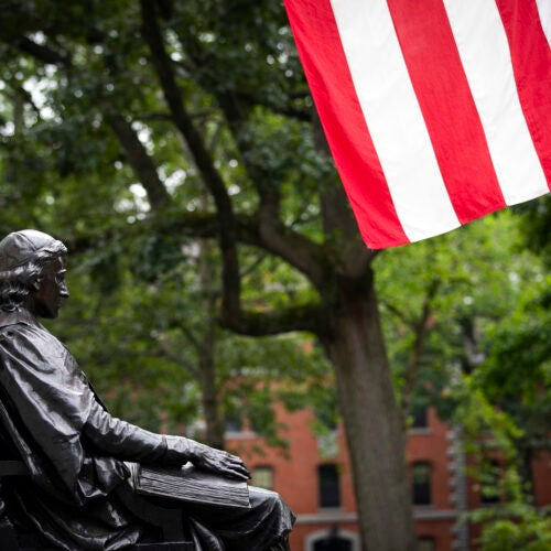 The John Harvard Statue is pictured with the American flat in Harvard Yard.