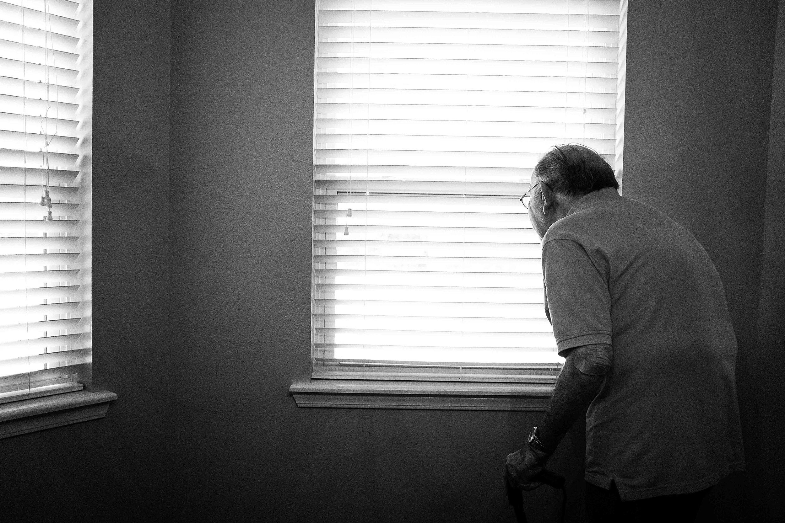 Older man looking out of window.