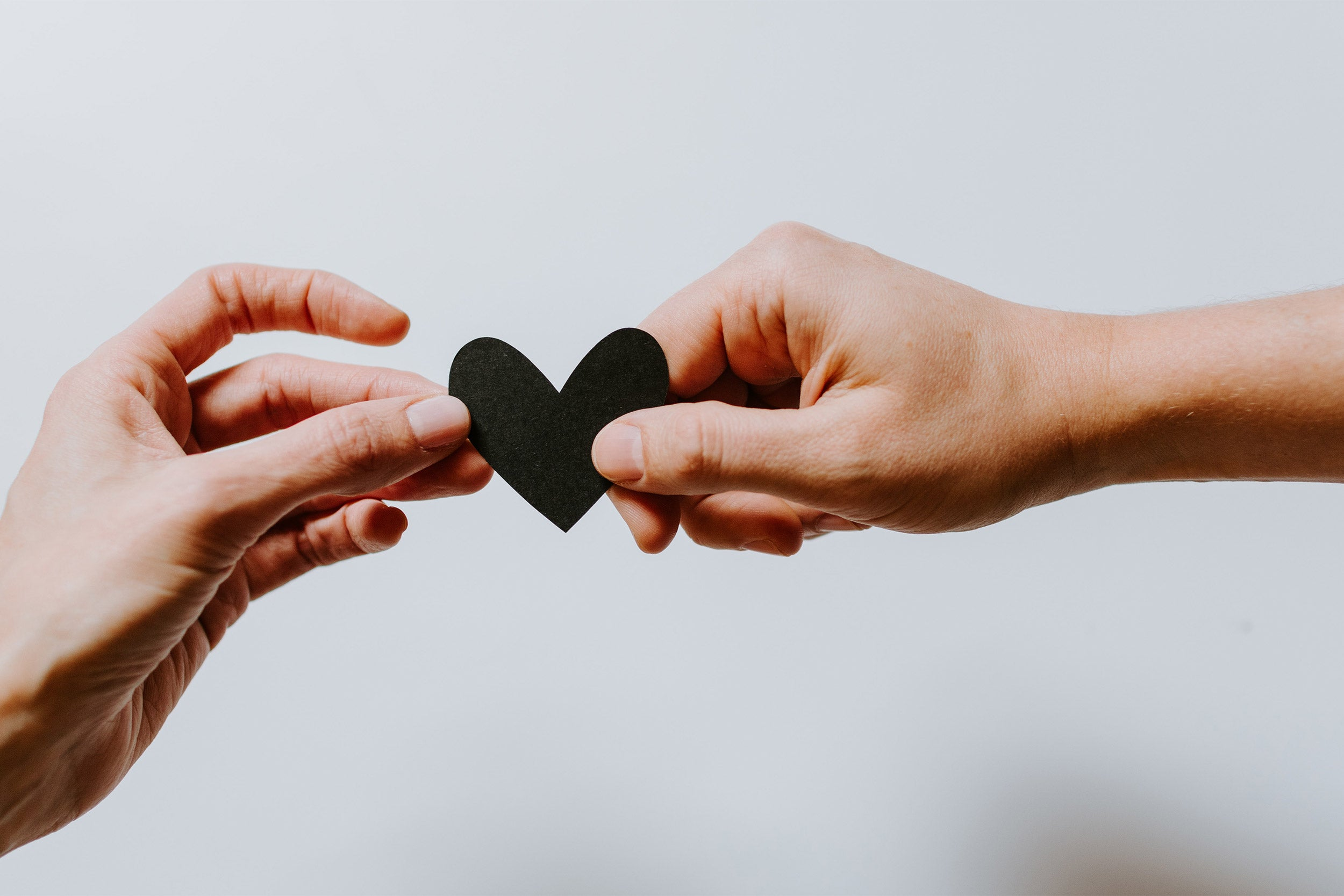 Two hands holding a single paper heart.
