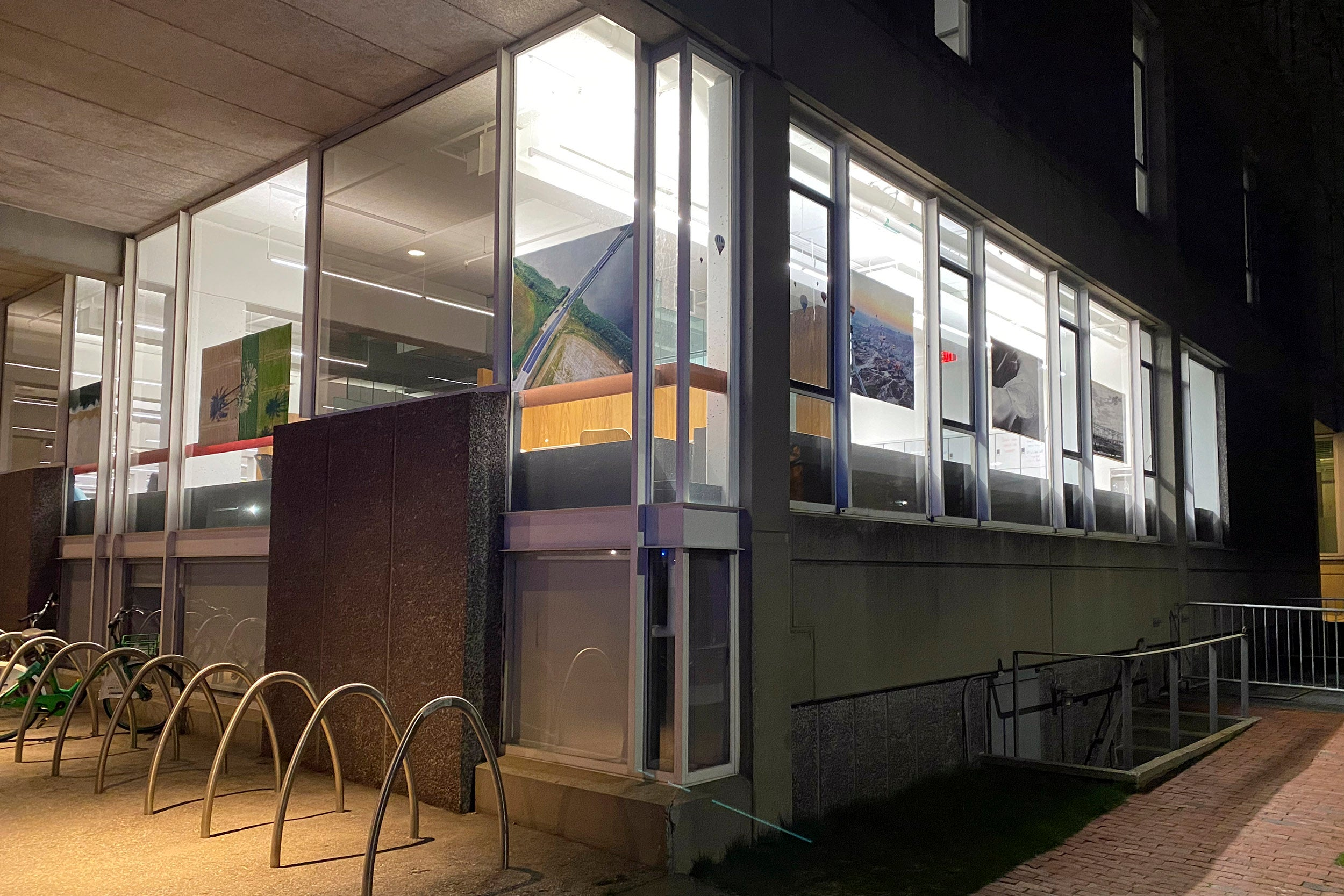 Art in windows of Cabot Library, lit up at night.