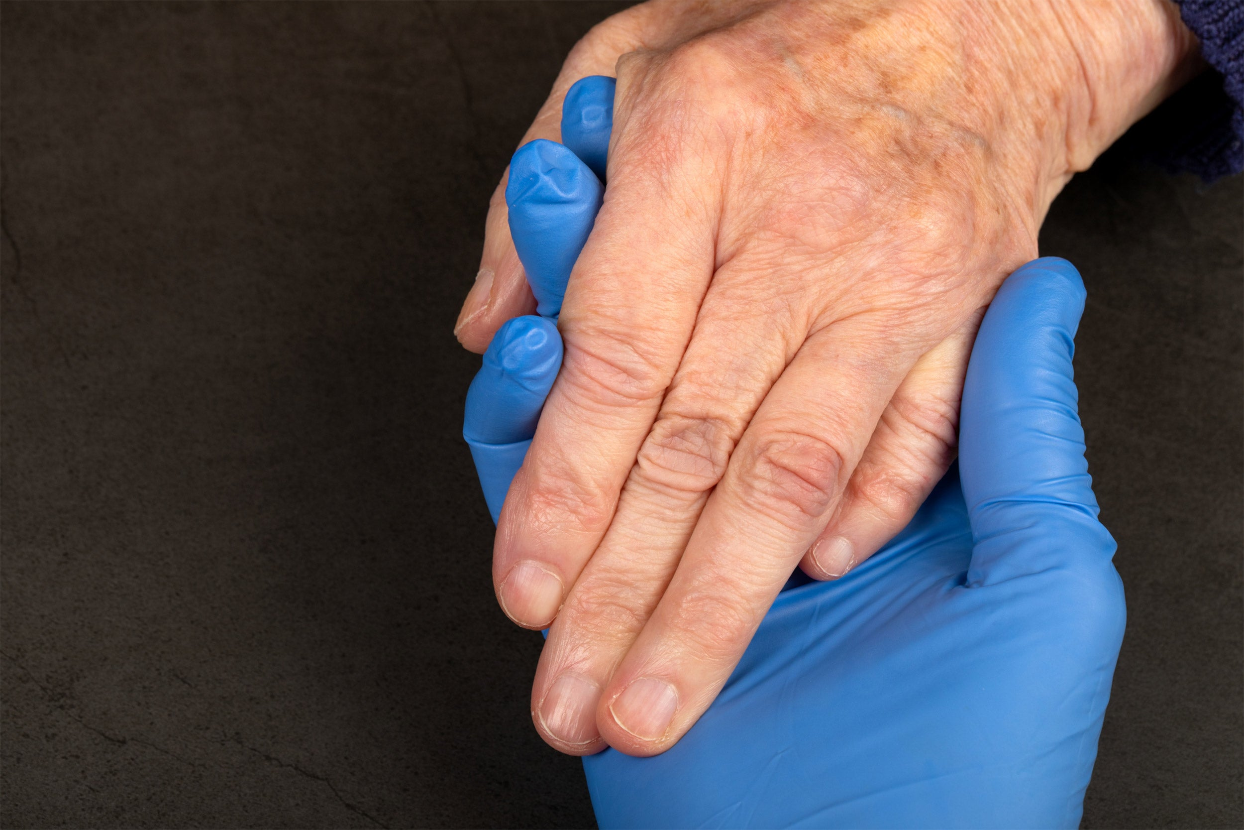 Caregiver holding elderly patients hand at home.