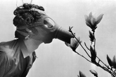 "Student in gas mask ""smalls"" a flower in New York on the first Earth Day."