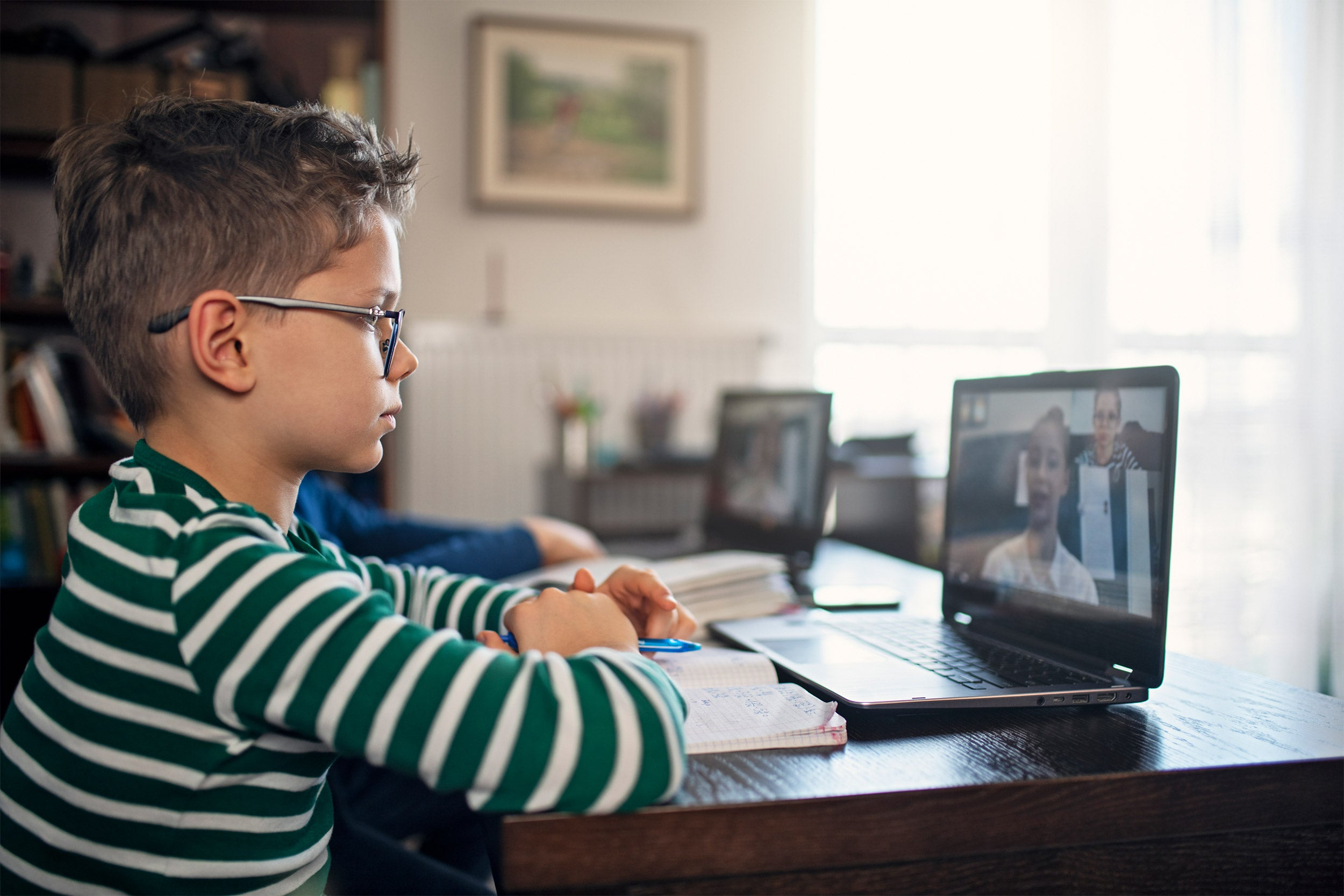 Little boys attending to online class from home.