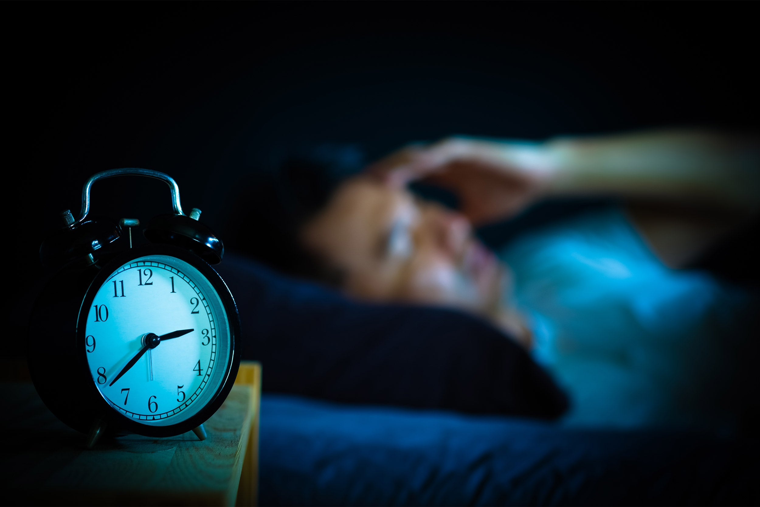 Man in bed suffering insomnia.