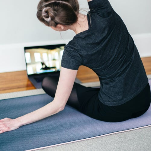 Woman doing yoga in front of laptop.