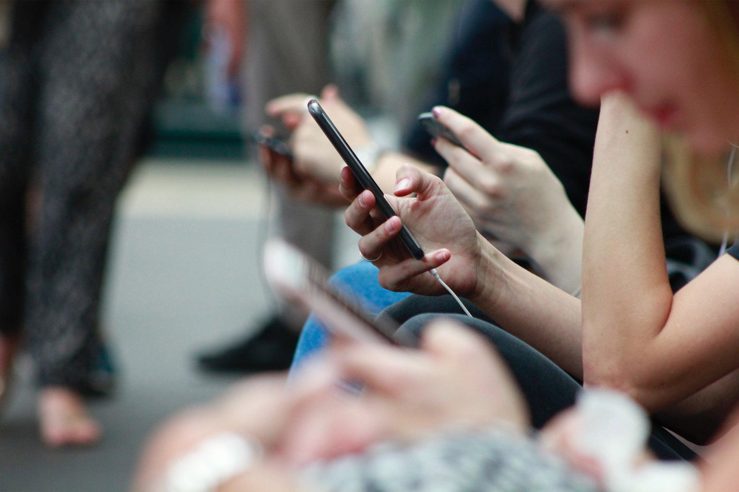 People looking at smartphones.