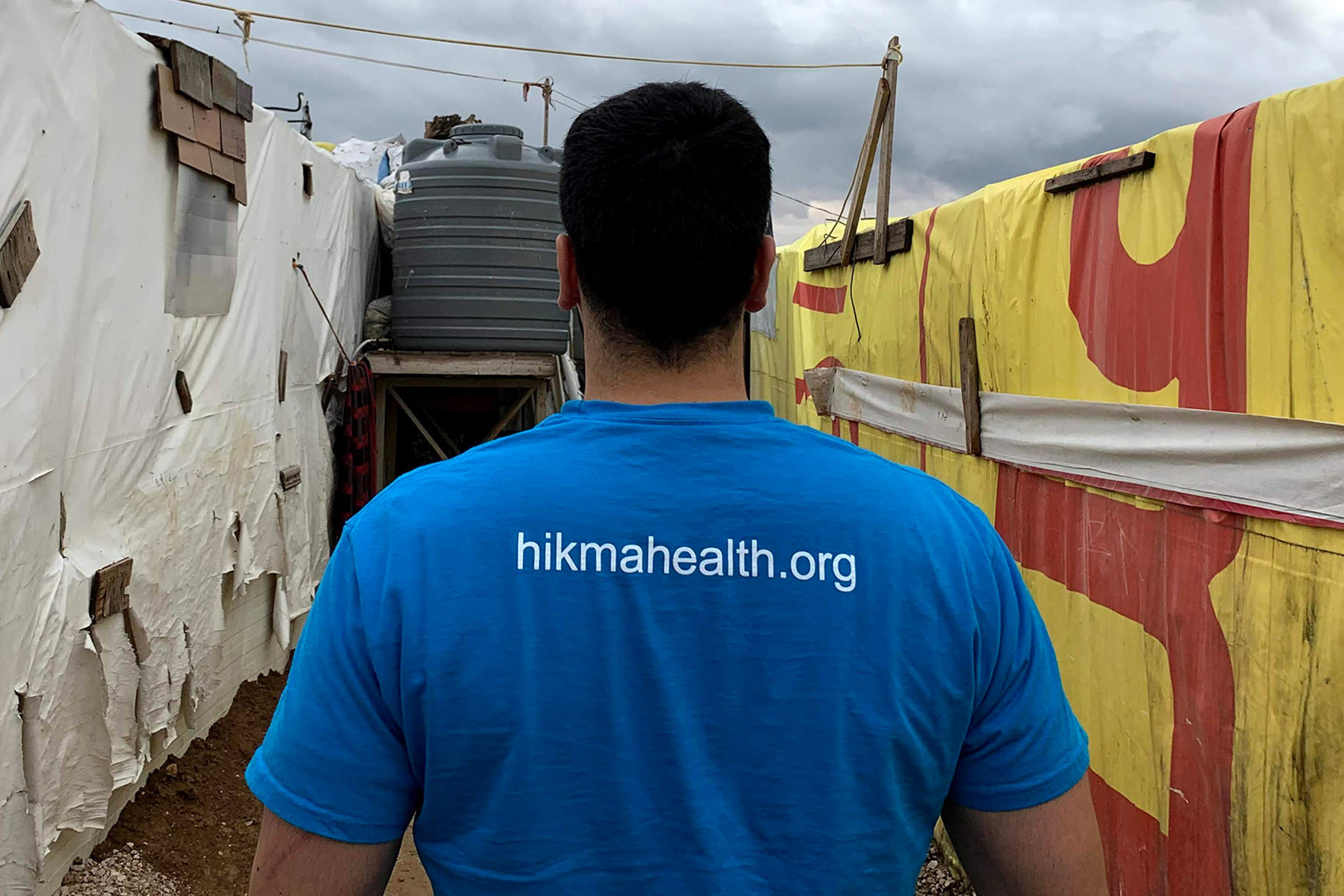 Man walking between tens in refugee camp.