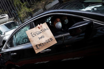 Man holding a protest sign from car.