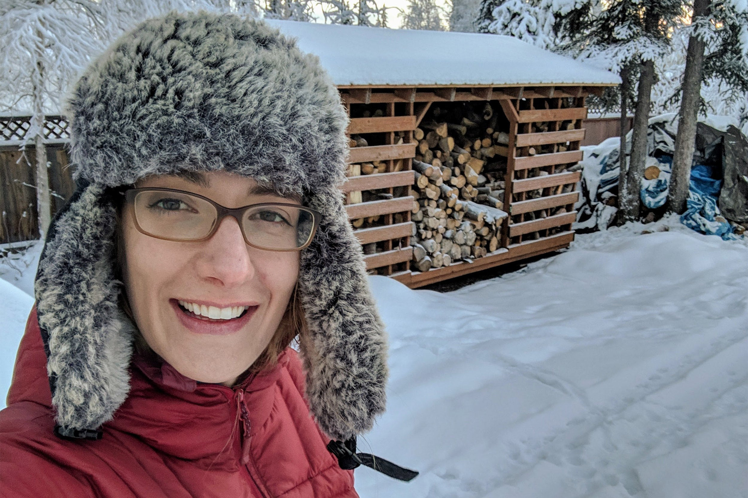 Alicia Nelson, M.P.H. '20 in front of woodpile.