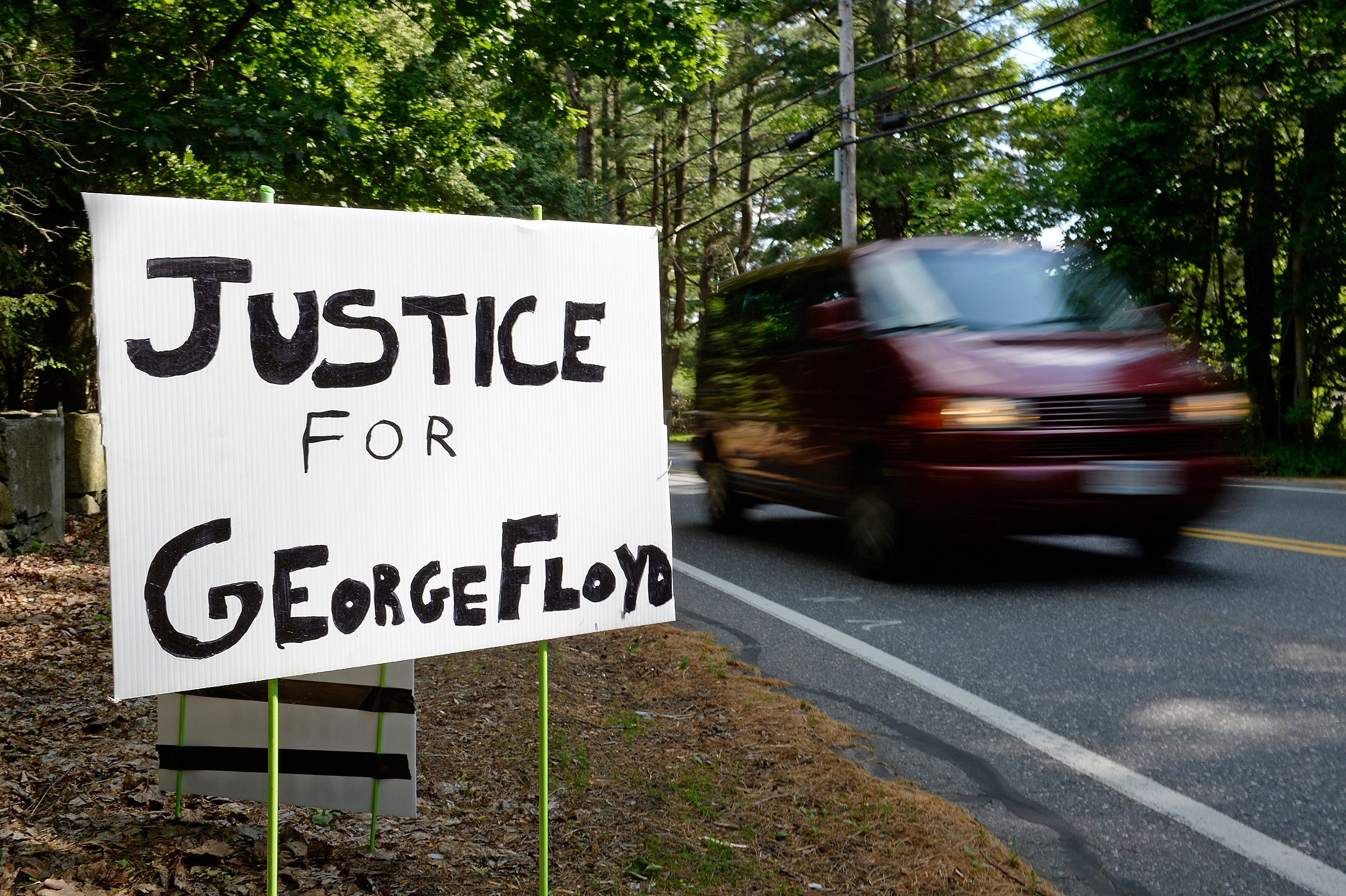 A sign reads, Justice for George Floyd.