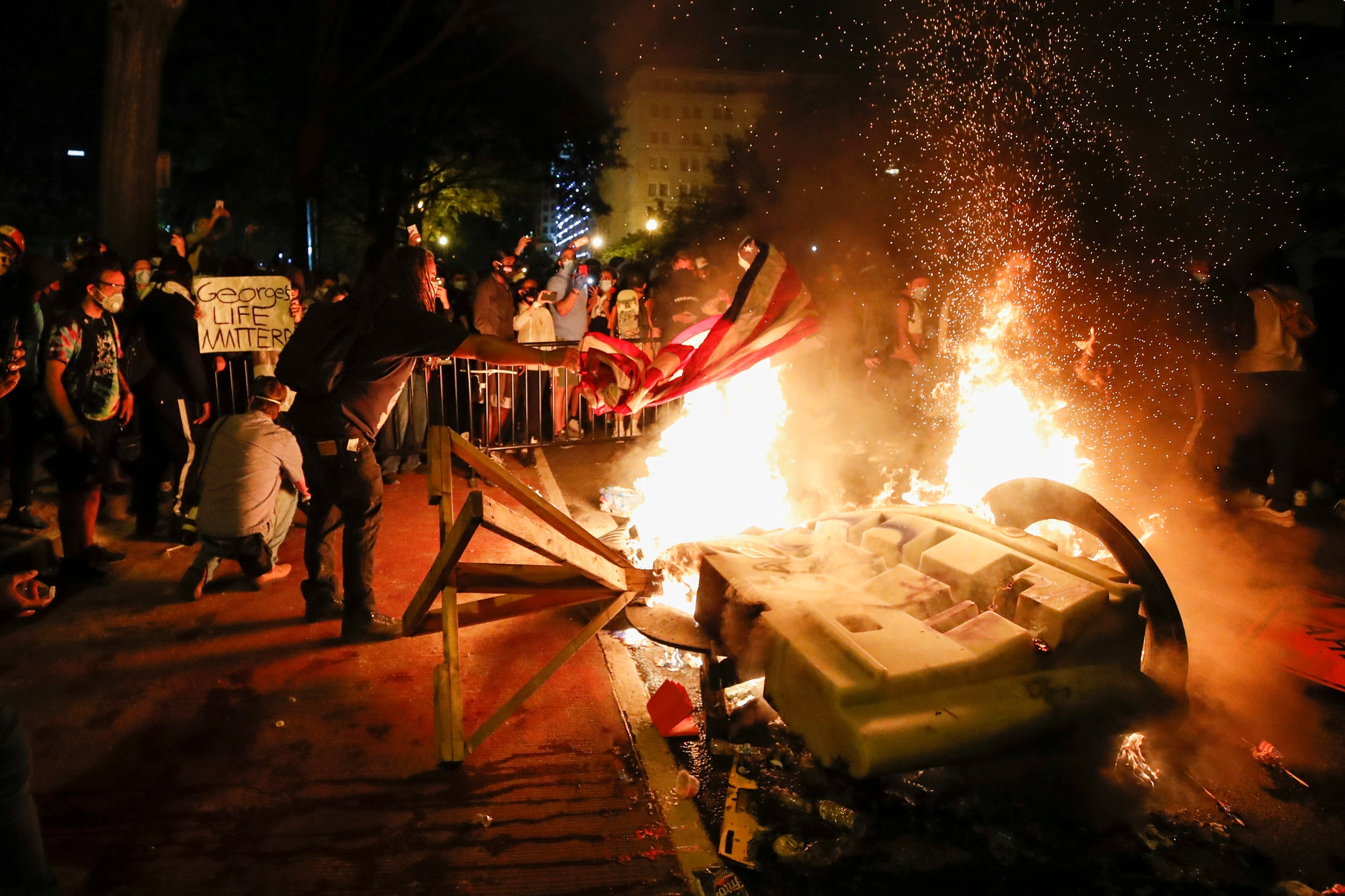 Fire burns during protest of police killing of George Floyd outside White House.